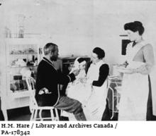 Image of Dr.Wilfred Grenfell examining patient at hospital, circa 1905-1915