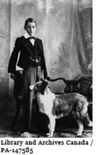 Image of Archie Belaney at the age of thirteen, standing next to a dog in 1901. Later, he became known as Grey Owl.